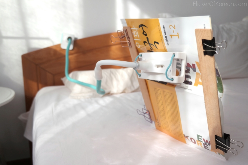 extended adjustable arm holding a textbook for reading in bed